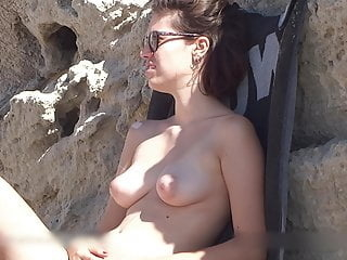Topless beach girl playing with her puffies